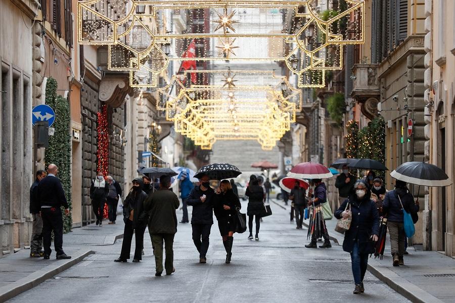 People wearing protective masks walk along Via dei Condotti street in Rome, Italy, 2 December 2020. (Yara Nardi/Reuters)