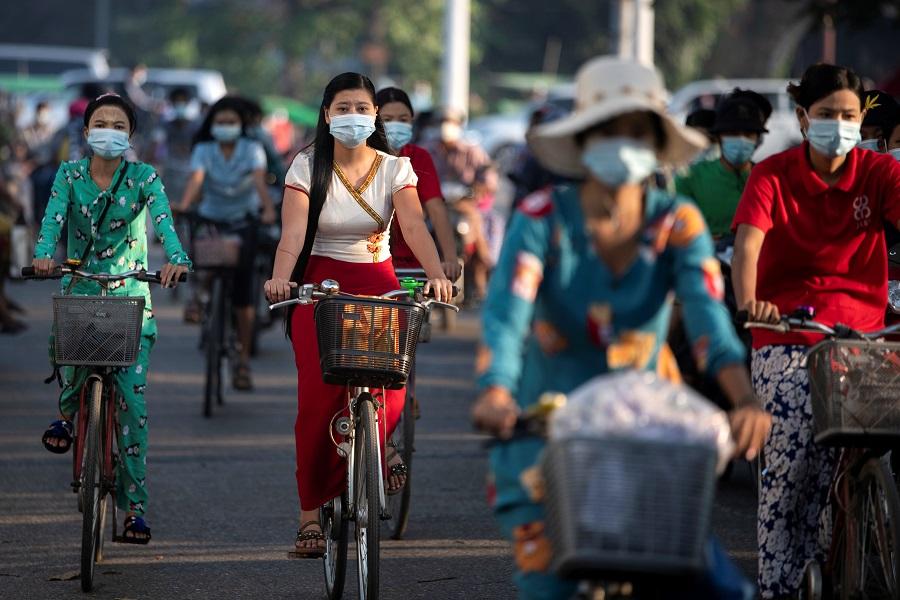 People wearing protective face masks ride bikes on a street in Yangon, Myanmar, 7 December 2020. (Shwe Paw Mya Tin/Reuters)