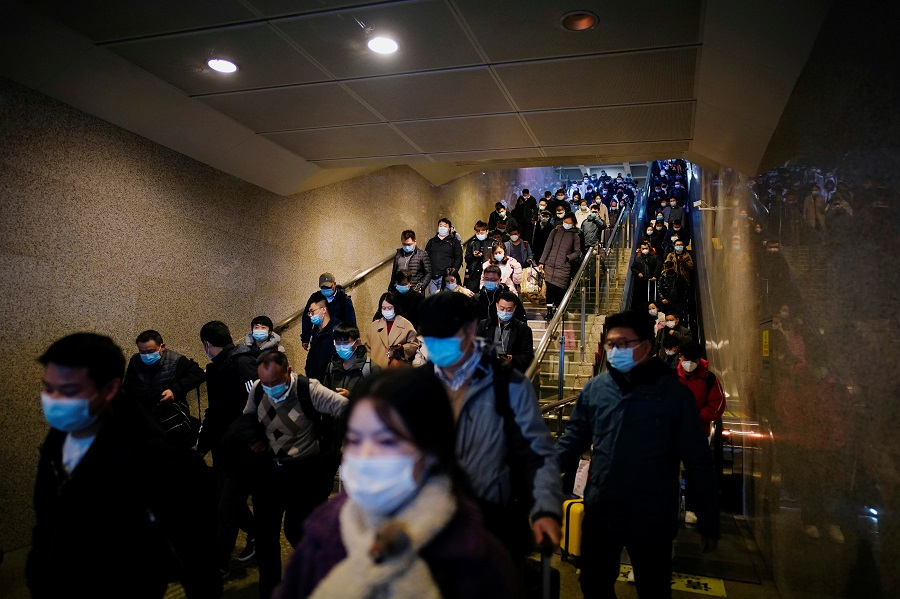 People wearing face masks arrive at a railway station in Wuhan, Hubei province, China, 6 December 2020. (Aly Song/Reuters)
