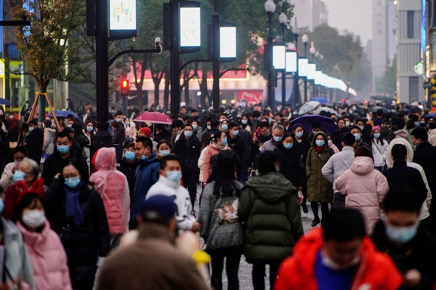 People wearing face masks are seen at a shopping area in Wuhan, Hubei province, China, 6 December 2020. (Aly Song/Reuters)