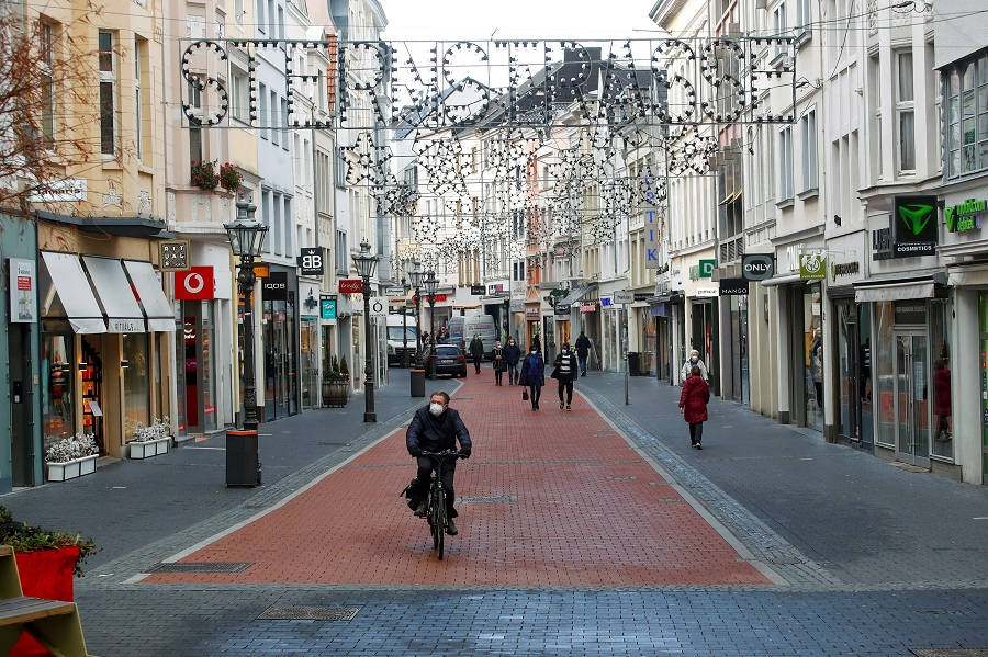 A man rides a bike through an almost deserted Sternstrasse (Star street)  shopping street, in Bonn, Germany, 16 December 2020. (Wolfgang Rattay/Reuters)