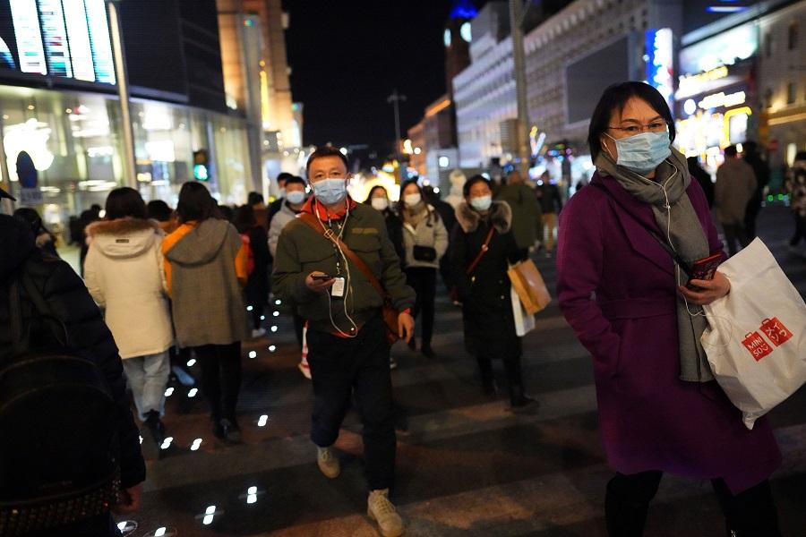 People walk along a shopping street in Beijing, China, 24 December 2020. (Tingshu Wang/Reuters)