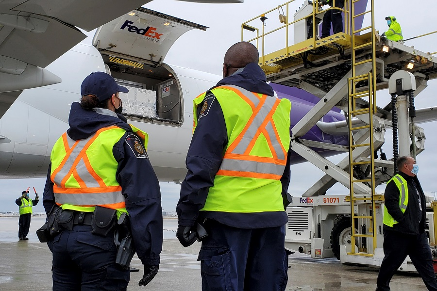 Canada Border Services Agency (CBSA) officers watch as the first shipment of newly authorised Moderna Covid-19 vaccine is unloaded from a Fedex cargo jet at a port of entry in Canada, 24 December 2020. (Canada Border Services Agency/Handout via Reuters)