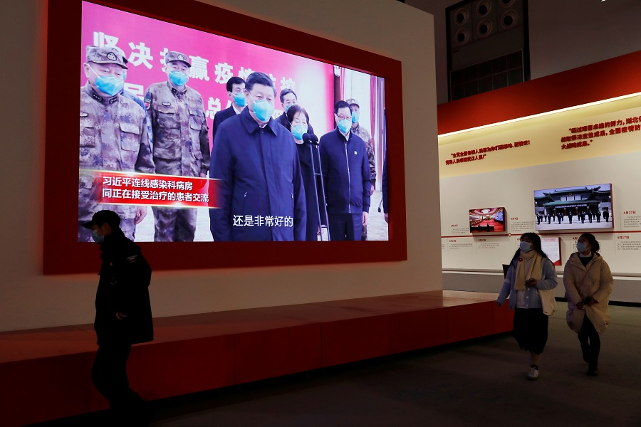 Visitors walk near a screen showing Chinese President Xi Jinping during an exhibition on the fight against the Covid-19 outbreak, at Wuhan Parlor Convention Center that previously served as a makeshift hospital for Covid-19 patients in Wuhan, Hubei province, China, 31 December 2020. REUTERS/Tingshu Wang/Reuters)