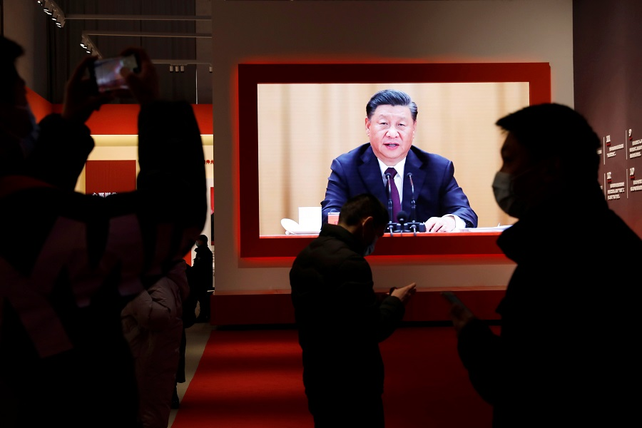 Visitors are seen near a screen showing Chinese President Xi Jinping during an exhibition on the fight against the Covid-19 outbreak, at Wuhan Parlor Convention Center that previously served as a makeshift hospital for Covid-19 patients in Wuhan, Hubei province, China, 31 December 2020. (Tingshu Wang/Reuters)
