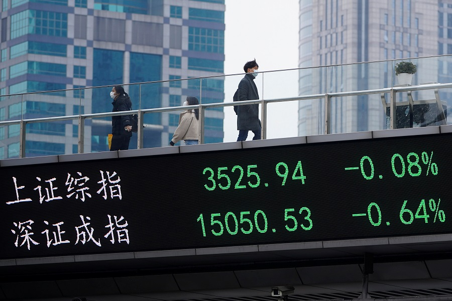 People wearing face masks walk on an overpass with an electronic board showing Shanghai and Shenzhen stock indexes, at the Lujiazui financial district in Shanghai, China, 6 January 2021. (Aly Song/Reuters)