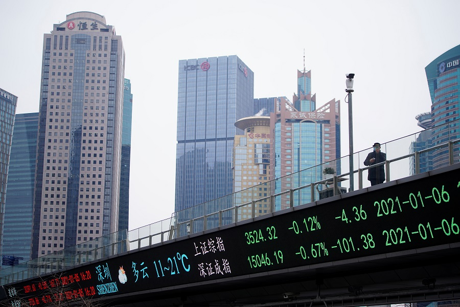 A man wearing a face mask stands on an overpass with an electronic board showing Shanghai and Shenzhen stock indexes, at the Lujiazui financial district in Shanghai, China, 6 January 2021. (Aly Song/Reuters)
