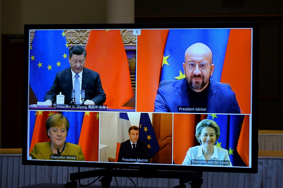 European Commission President Ursula von der Leyen, European Council President Charles Michel, German Chancellor Angela Merkel, French President Emmanuel Macron and Chinese President Xi Jinping are seen on a screen during a video conference, in Brussels, Belgium, 30 December 2020. (Johanna Geron/Pool/File Photo/Reuters)