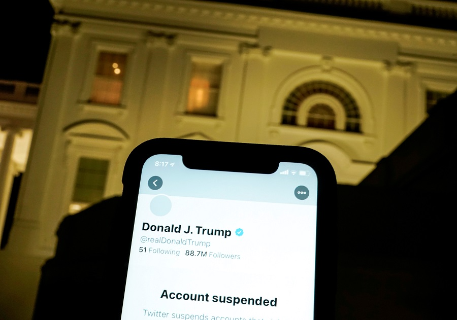 A photo illustration shows the suspended Twitter account of former US President Donald Trump on a smartphone and the White House in Washington, US, 8 January 2021. (Joshua Roberts/Illustration/File Photo/Reuters)