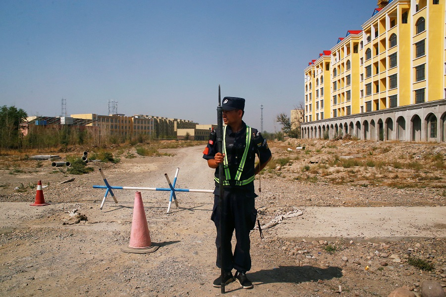 A Chinese police officer takes his position by the road near what is officially called a vocational education center in Yining in Xinjiang Uighur Autonomous Region, China, 4 September 2018. (Thomas Peter/File Photo/Reuters)