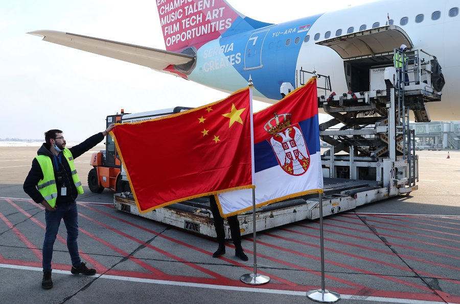 A man holds China's flag next to Serbia's flag as a plane transporting one million doses of Sinopharm's China National Biotec Group (CNBG) vaccines for the Covid-19 coronavirus arrives at Nikola Tesla Airport in Belgrade, Serbia, 16 January 2021. (Marko Djurica/Reuters)