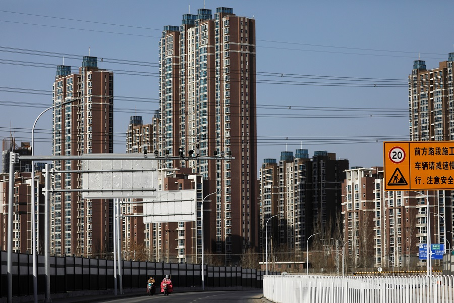 People ride scooters past residential buildings in Beijing, China, 13 January 2021. (Tingshu Wang/Reuters)