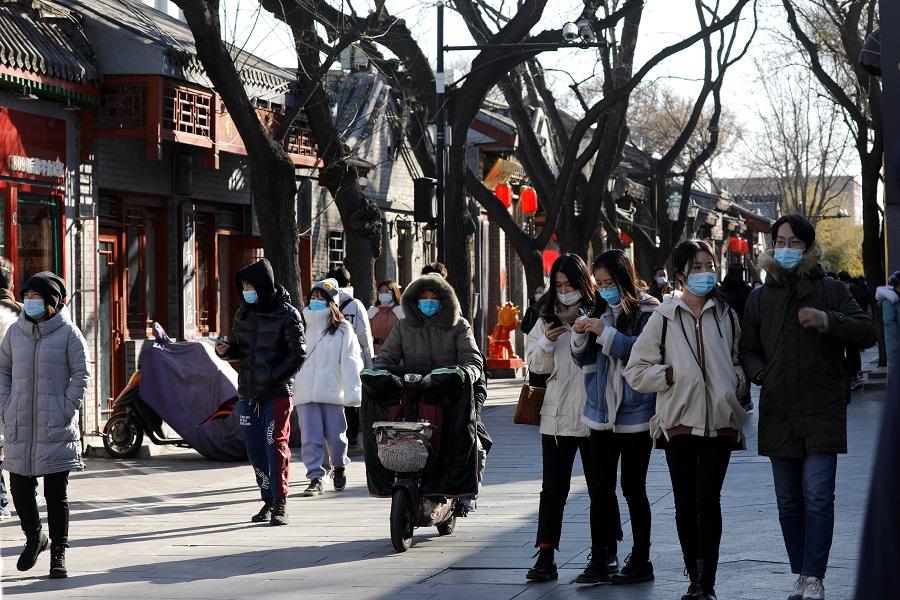 People wearing face masks walk along Nanluoguxiang alley, in Beijing, China, 16 January 2021. (Tingshu Wang/Reuters)