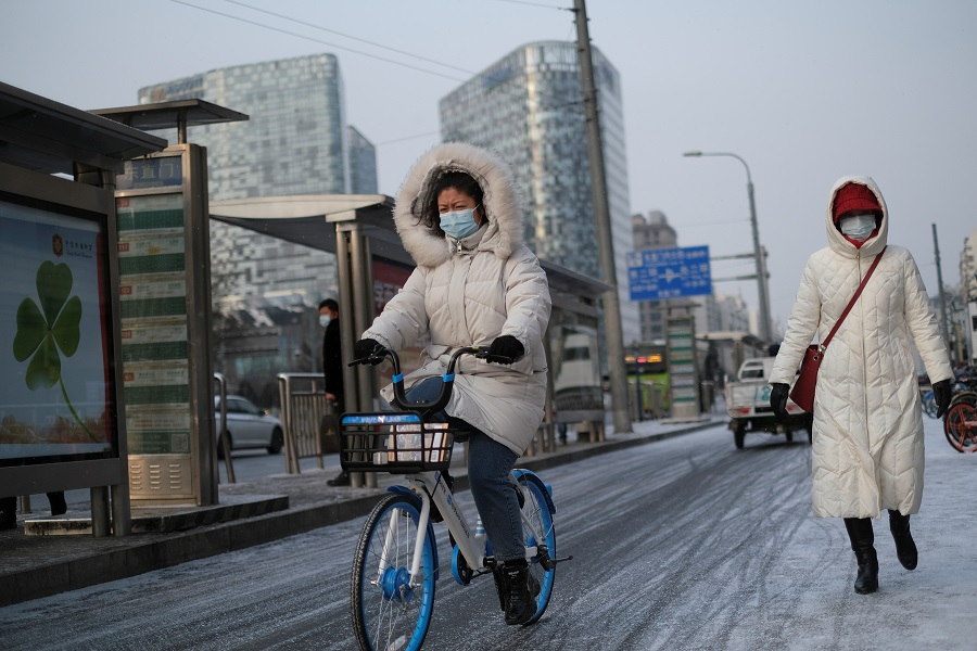 A woman wearing a face mask rides a bicycle on the street during a snowy morning in Beijing, China, 19 January 2021. (Carlos Garcia Rawlins/Reuters)