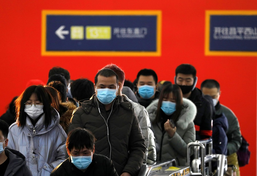 People wearing face masks commute in a subway station during morning rush hour in Beijing, China, 20 January 2021. (Tingshu Wang/Reuters)