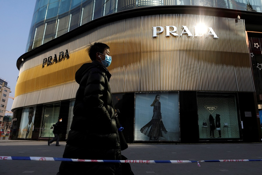 A man wearing a face mask walks past a store of Italian luxury brand Prada on a shopping street in Beijing, China, 20 January 2021. (Tingshu Wang/Reuters)