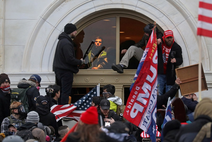 A mob of supporters of then US President Donald Trump climb through a window they broke as they storm the US Capitol Building in Washington, US, 6 January 2021. (Leah Millis/File Photo/Reuters)