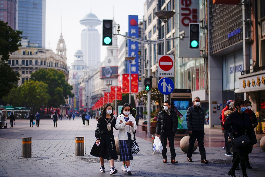 People wearing face masks walk at a shopping area in Shanghai, China, 27 January 2021. (Aly Song/Reuters)