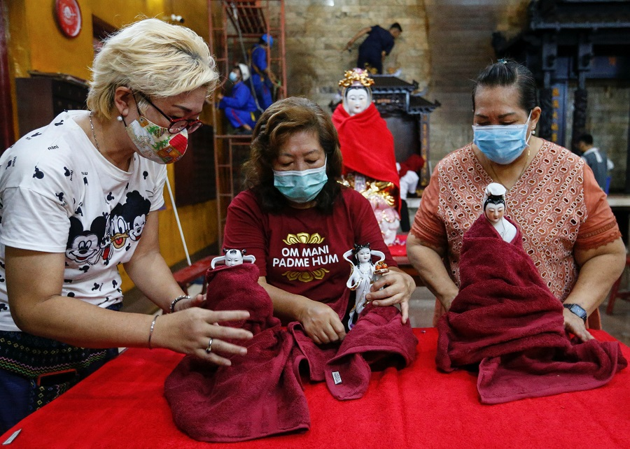 Women wearing protective face masks wipe religious figurines ahead of the Lunar New Year celebrations, at a temple in Jakarta, Indonesia, 4 February 2021. (Ajeng Dinar Ulfiana/Reuters)