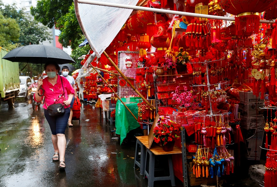 A woman wearing a protective mask carries an umbrella as she walks past a stall selling decorations at a street market ahead of the Lunar New Year, in Jakarta, Indonesia, 4 February 2021. (Ajeng Dinar Ulfiana/Reuters)