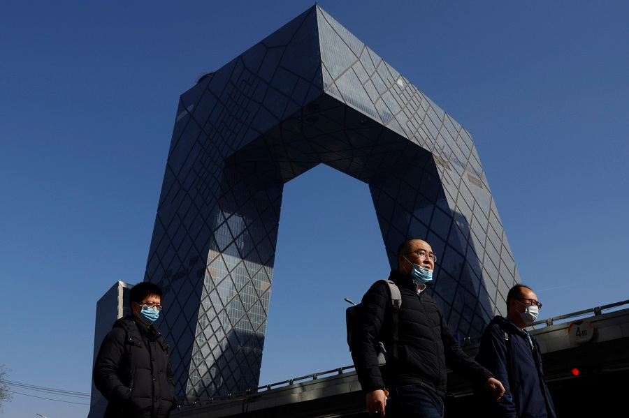 People wearing face masks walk past the CCTV headquarters, home of Chinese state media outlet CCTV and its English-language sister channel CGTN, in Beijing, China, 5 February 2021. (Carlos Garcia Rawlins/Reuters)