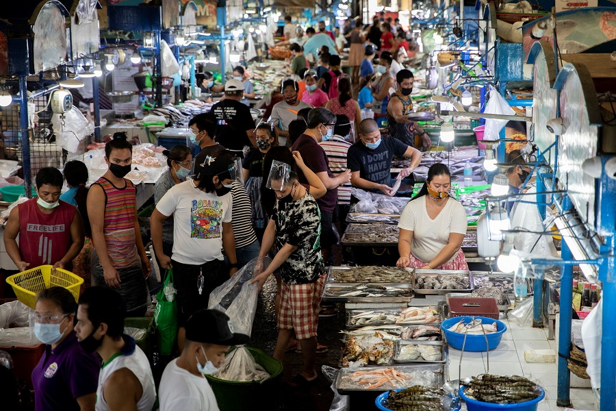 Vendors and customers wearing face masks are seen inside a public market in Quezon City, Metro Manila, the Philippines, 5 February 2021. (Eloisa Lopez/Reuters)