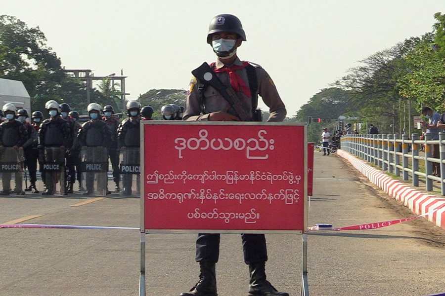 "A policeman stands behind a banner reading ""if this line is crossed, Myanmar police force will fire with live ammunition"" during protests against the military coup and to demand the release of elected leader Aung San Suu Kyi, in Nay Pyi Taw, Myanmar, 8 February 2021. (Stringer/File Photo/Reuters)"