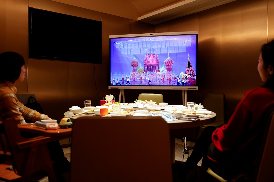 A family watches the New Year Gala after having dinner at a Haidilao hotpot restaurant, in Beijing, China, 11 February 2021. (Carlos Garcia Rawlins/Reuters)