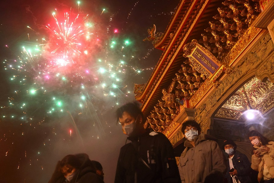 People watch Lunar New Year fireworks while wearing protective masks as they wait to enter a temple in Taipei, Taiwan, 12 February 2021. (Ann Wang/Reuters)