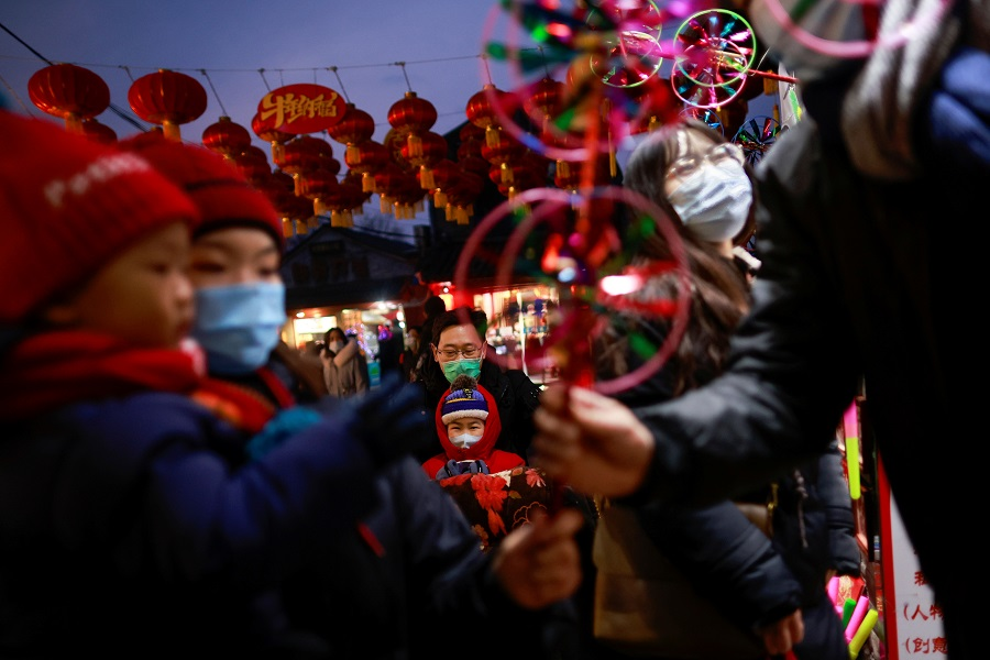 People stand with children in front of a souvenier shop in a historic part of Beijing, China, 14 February 2021. (Thomas Peter/Reuters)
