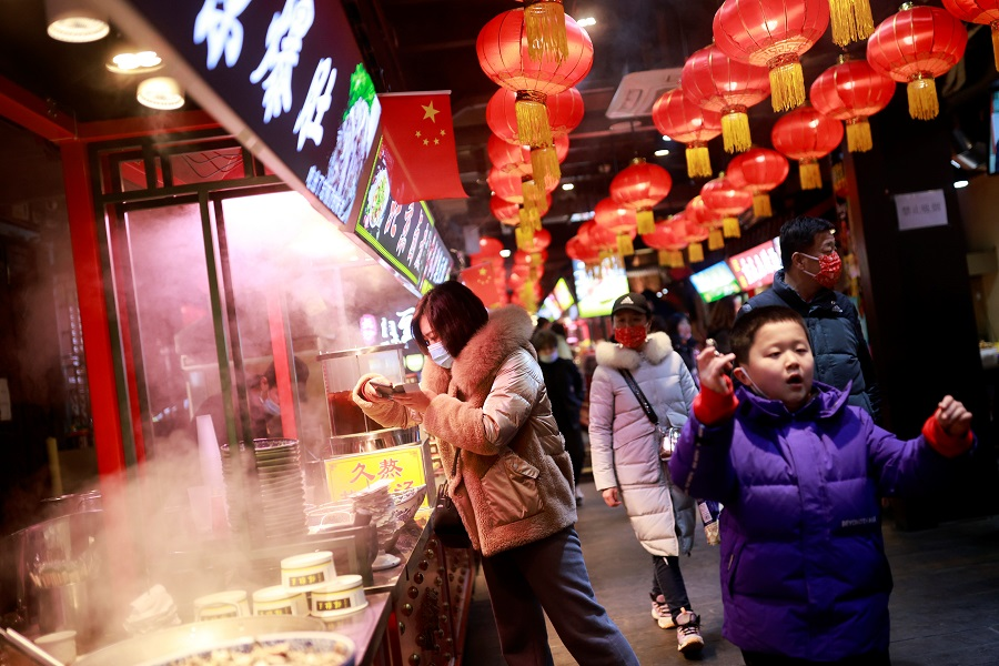 People walk in a historic part of Beijing as China celebrates Lunar New Year, China, 14 February 2021. (Thomas Peter/Reuters)