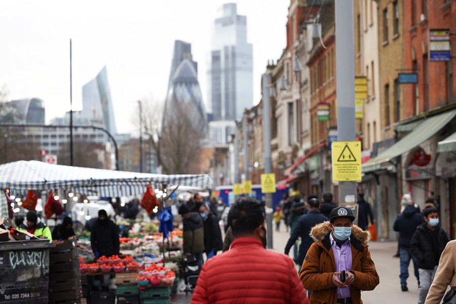 People walk past shops and market stalls, amid the Covid-19 outbreak in London, Britain, 15 February 2021. (Henry Nicholls/Reuters)