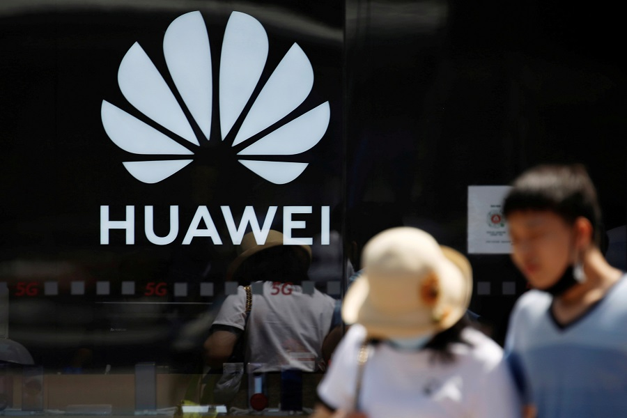 People walk past a Huawei logo on the facade of its store at a shopping complex in Beijing, China, 14 July 2020. (Tingshu Wang/File Photo/Reuters)