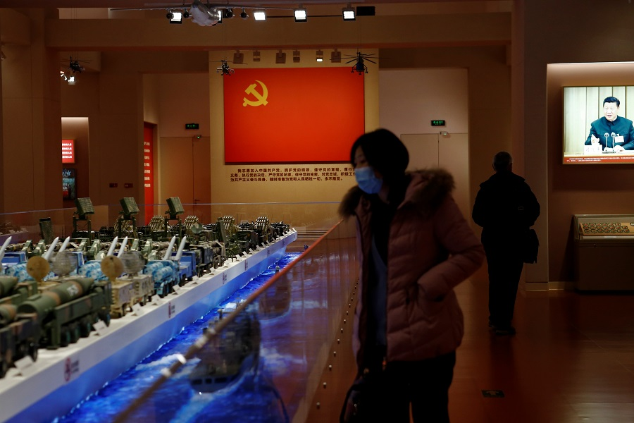 A visitor looks at models of Chinese military equipment in front of an exhibit of the Chinese Communist Party flag at an exhibition at the National Museum of China in Beijing, China, 3 March 2021. (Tingshu Wang/Reuters)