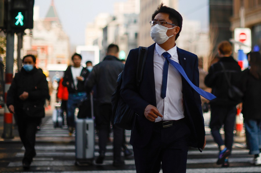 A man wearing a face mask walks on a street in Shanghai, China, 4 March 2021. (Aly Song/Reuters)
