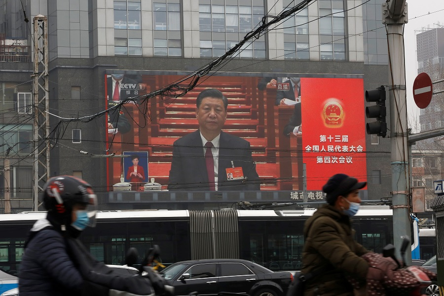 A giant screen shows Chinese President Xi Jinping attending the opening session of the National People's Congress (NPC) at the Great Hall of the People, in Beijing, China, 5 March 2021. (Tingshu Wang/Reuters)