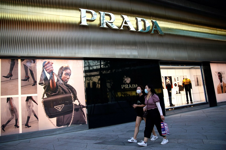 People wearing face masks walk past a store of Italian luxury brand Prada at a shopping complex in Beijing, China, 19 September 2020. (Tingshu Wang/File Photo/Reuters)