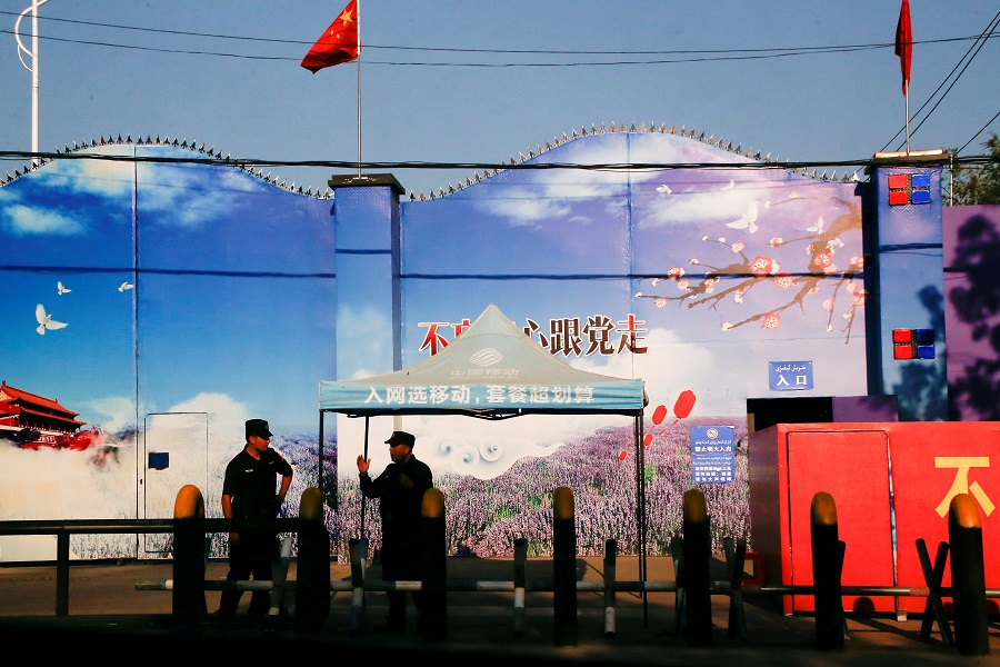 Security guards stand at the gates of what is officially known as a vocational skills education centre in Huocheng County in Xinjiang Uighur Autonomous Region, China, 3 September 2018. (Thomas Peter/File Photo/Reuters)