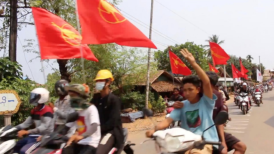 Protesters fly the flags of the National League for Democracy (NLD) as they ride their motorcycles in Dawei district, Myanmar, 16 March 2021, in this still image obtained from a video. (Courtesy of Dawei Watch via Reuters)