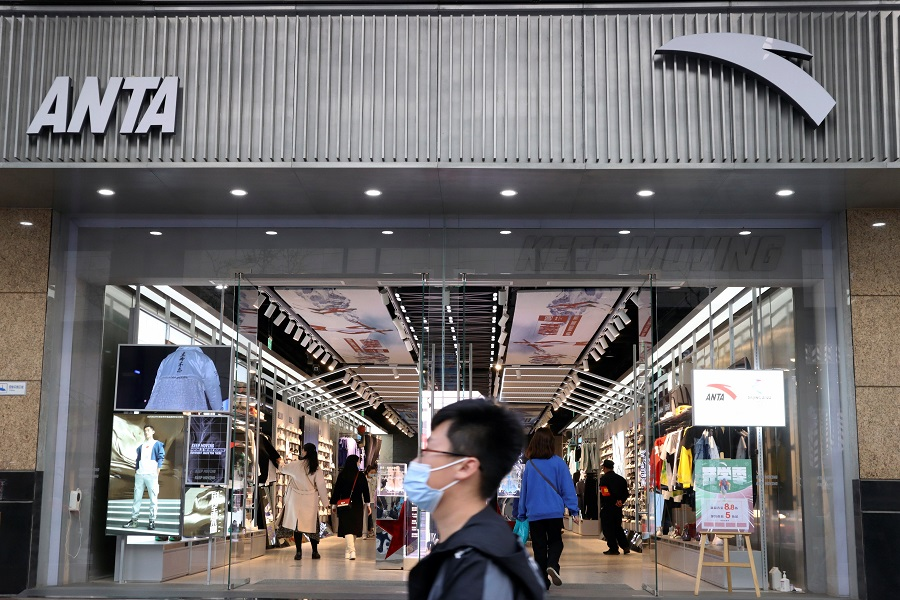 A man walks past a store of Chinese sportswear firm Anta Sports at a shopping mall in Beijing, China, 25 March 2021. (Florence Lo/Reuters)