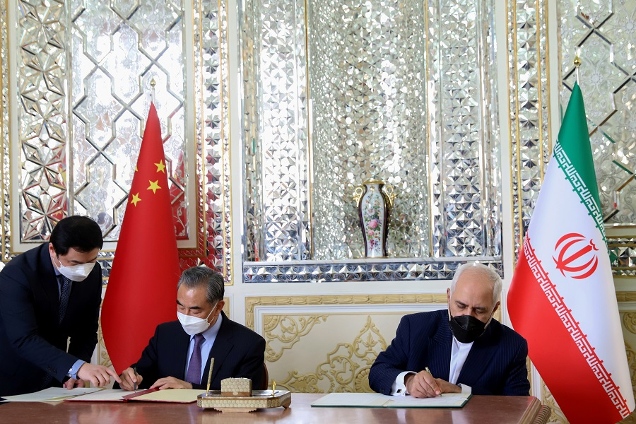 Iran's Foreign Minister Mohammad Javad Zarif and China's Foreign Minister Wang Yi sign a 25-year cooperation agreement in Tehran, Iran, 27 March 2021. (Majid Asgaripour/West Asia News Agency via Reuters)