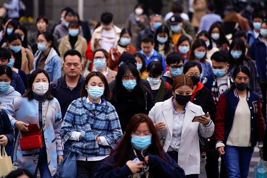 People wearing face masks walk on a street in Shanghai, China, 30 March 2021. (Aly Song/Reuters)