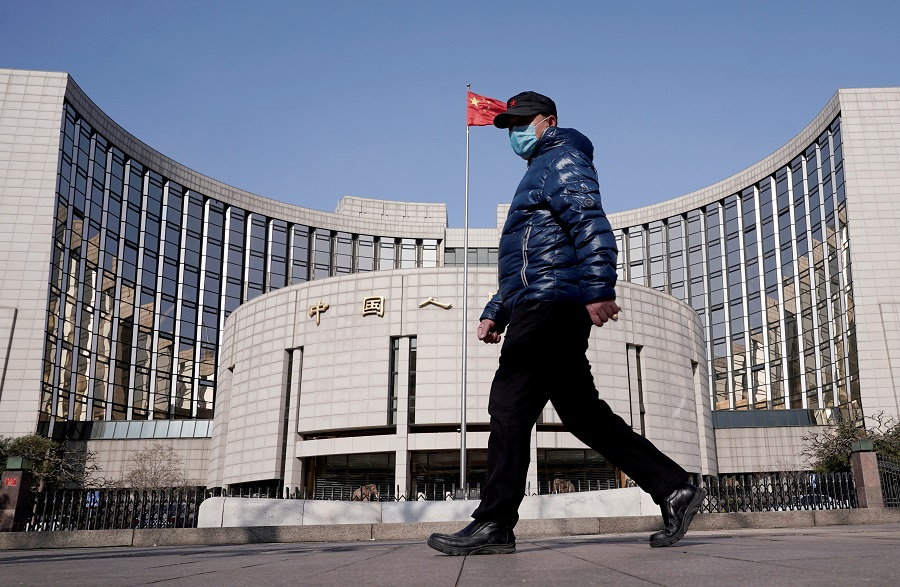 A man wearing a mask walks past the headquarters of the People's Bank of China, in Beijing, China, 3 February 2020. (Jason Lee/File Photo/Reuters)