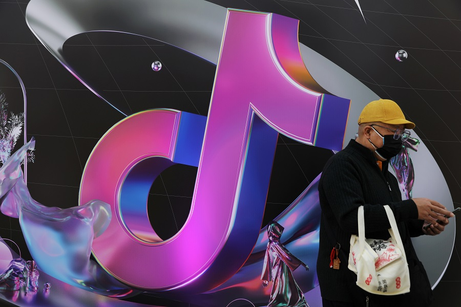 A man stands near a giant sign of Chinese company ByteDance's app TikTok, known locally as Douyin, in Beijing, China, 31 March 2021. (Tingshu Wang/File Photo/Reuters)