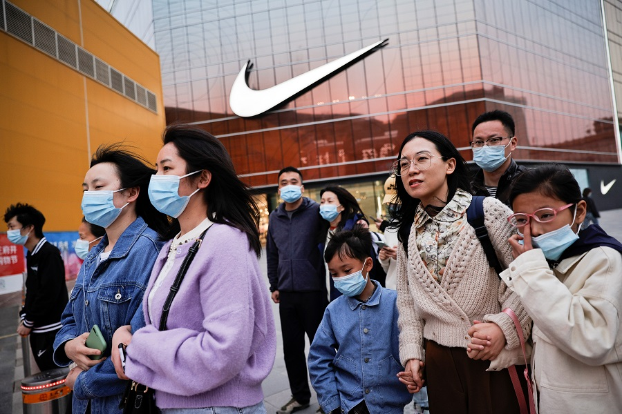 People walk in a shopping district in Beijing, China, 5 April 2021. (Thomas Peter/Reuters)