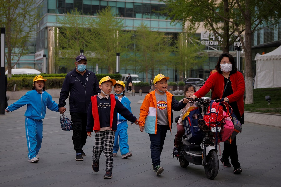 People pick up children from a school in Beijing, China, 6 April 2021. (Thomas Peter/Reuters)