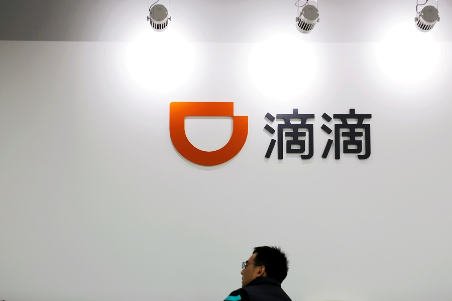 A man is seen under a Didi logo at the headquarters of Didi Chuxing in Beijing, China, 20 November 2020. (Florence Lo/File Photo/Reuters)