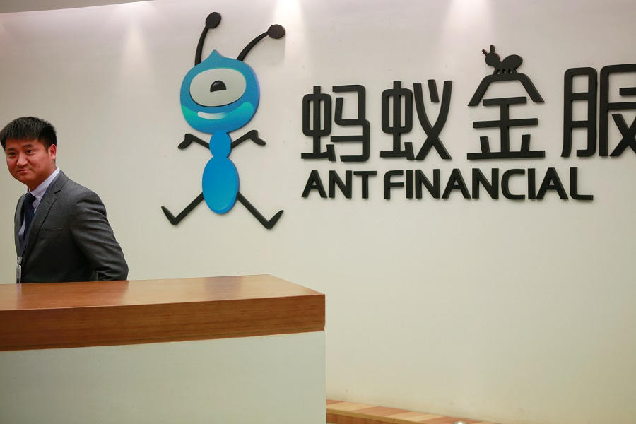 An employee stands next to the logo of Ant Financial Services Group, Alibaba's financial affiliate, at its headquarters in Hangzhou, Zhejiang province, China, 24 January 2018. (Shu Zhang/File Photo/Reuters)