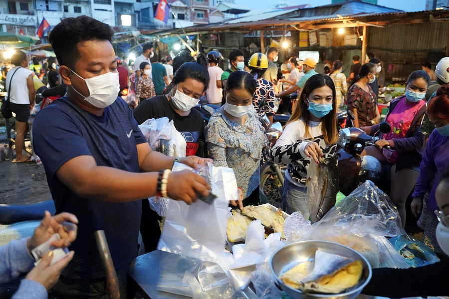 People wearing protective face masks buy groceries at a fresh market at a temple in Phnom Penh, Cambodia, 14 April 2021. (Cindy Liu/Reuters)