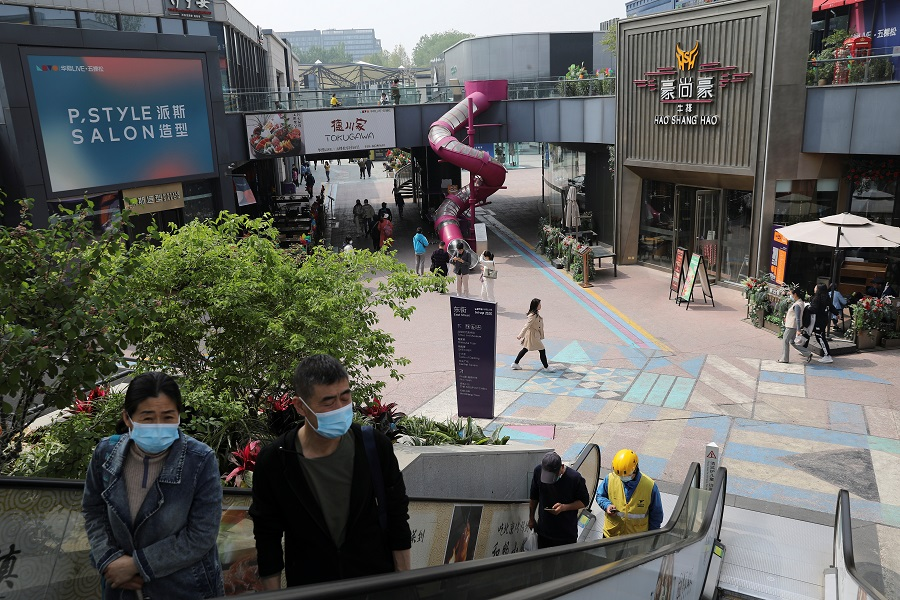 People visit a shopping complex in Beijing, China, 15 April 2021. (Tingshu Wang/Reuters)
